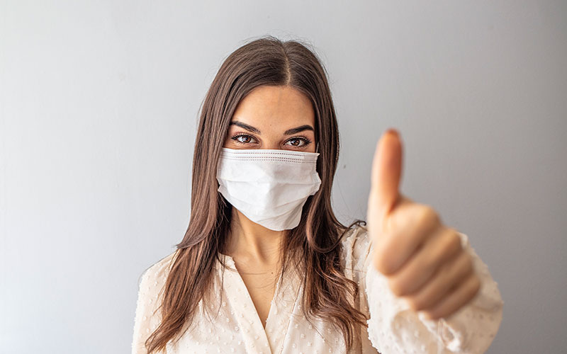 Woman giving thumbs up with a mask on her face