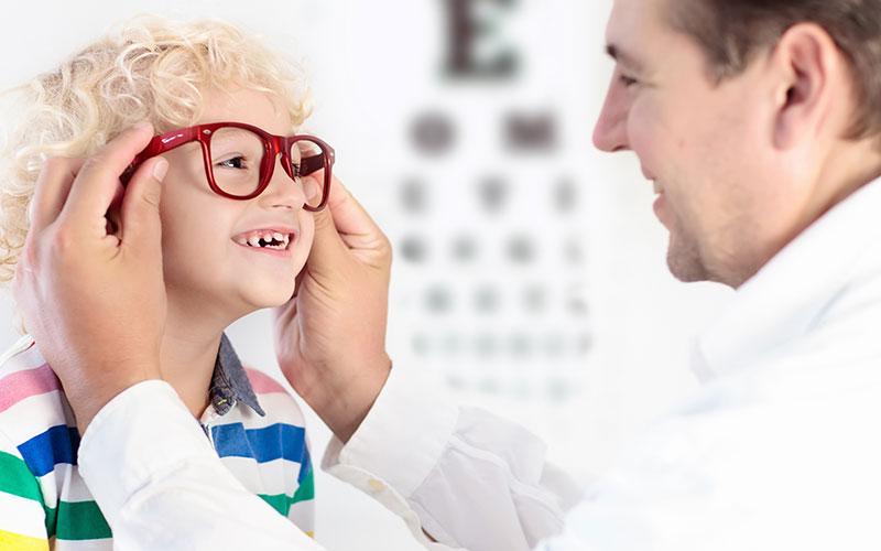 Image of a child and an eye doctor getting glasses fitted