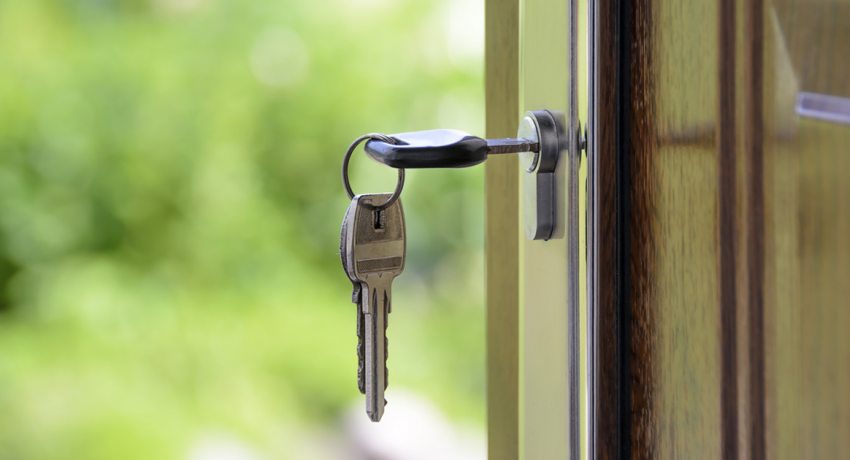Keys in a door to illustrate the decision to rent vs buy a home
