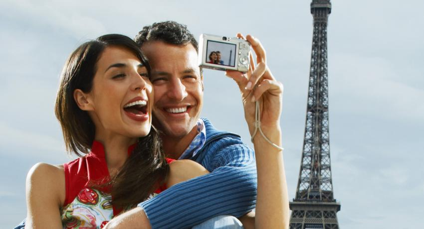 Couple in front of the Eiffel Tower illustrating that travel and saving don't have to be mutually exclusive.