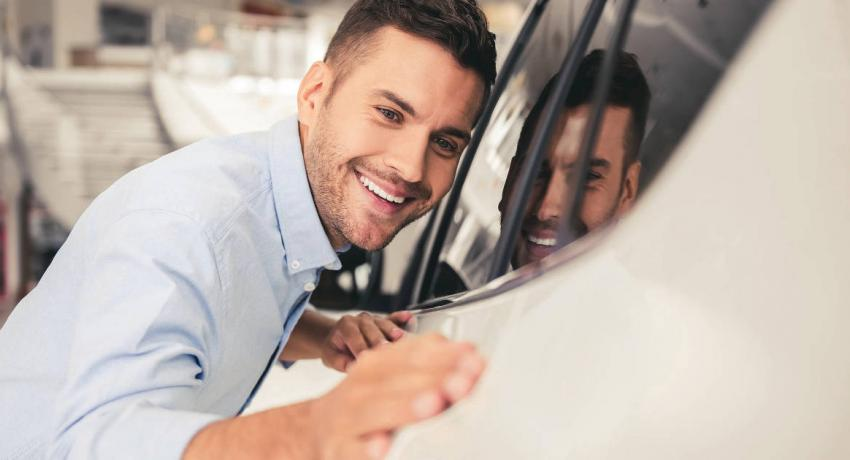 Man admiring a new car and considering the daily expenses of owning a car.