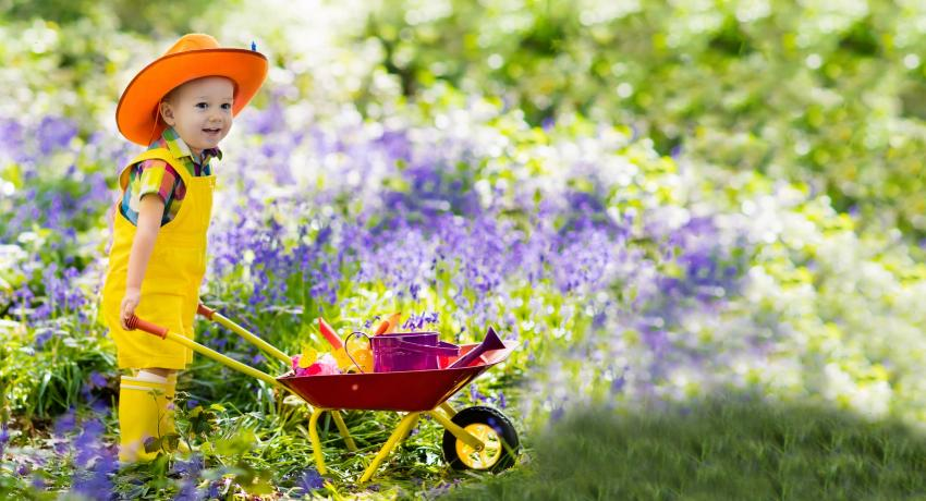 Child in cowboy hat pushing a wheelbarrow