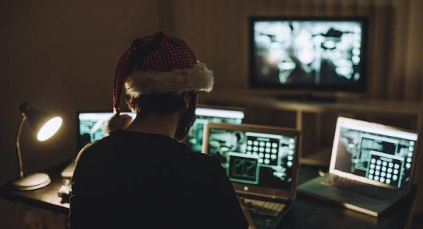 man in santa hat looking at holiday scams on computers