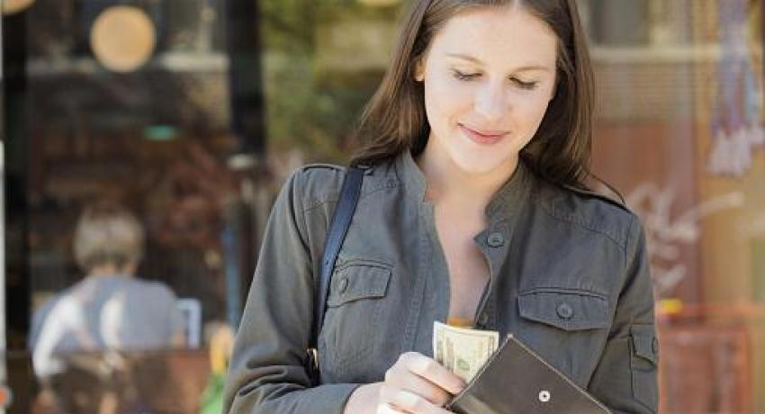 woman putting cash in wallet