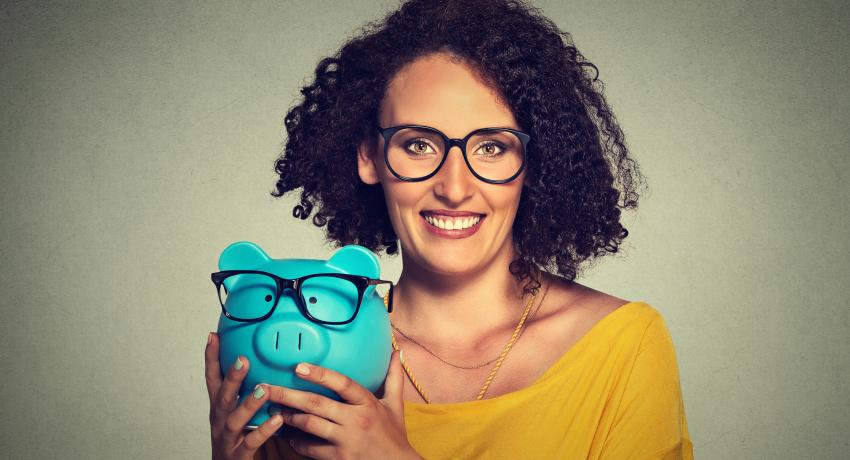 woman wearing glasses holding a piggy bank