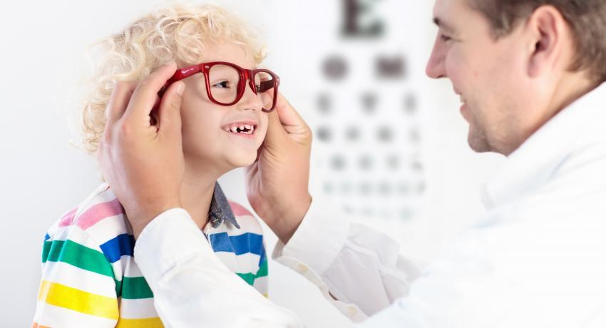 child trying on glasses at eye doctor