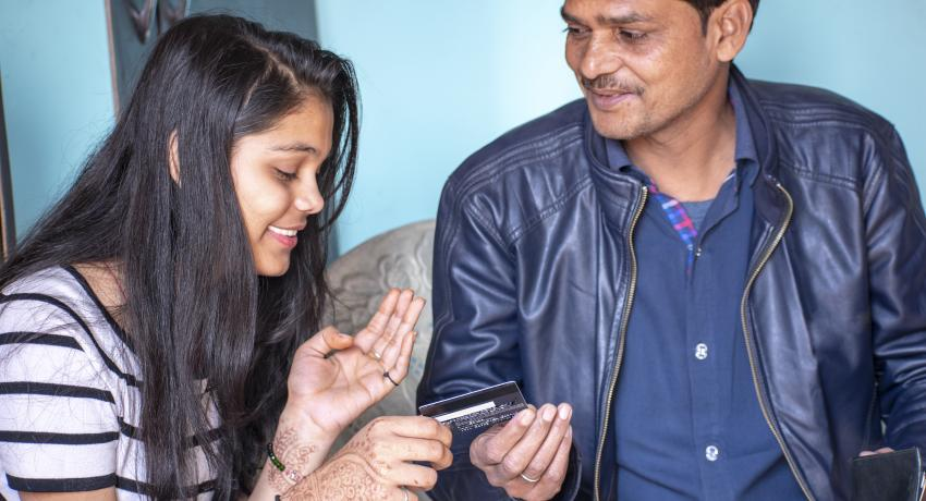 father and daughter holding credit card