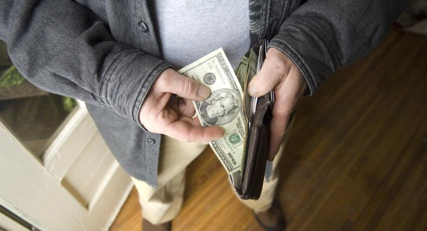 man's hands putting money in wallet