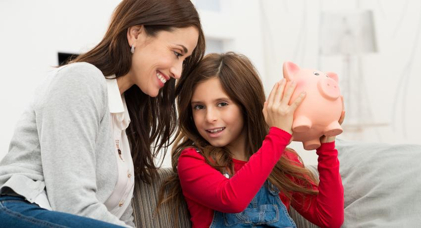 mom and daughter holding piggy bank